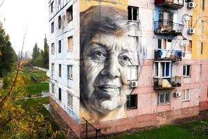 Портрет учительки настіні будинку дивиться вбік окупантів