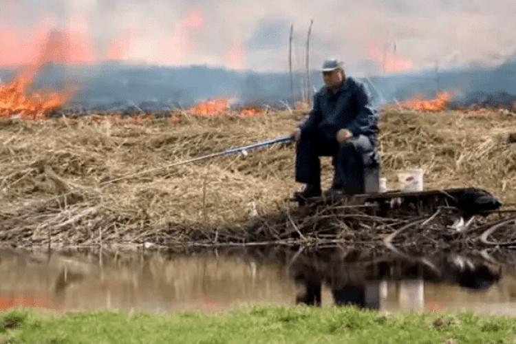 У мережі набирає популярність відео, де чоловік спокійно ловить рибу на тлі бурхливої пожежі