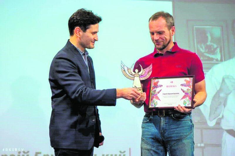 Ахтем Сеітаблаєв (ліворуч) вручає статуетку Янгола— Волонтерську премію 2020року— тренеру зЛадижина.
