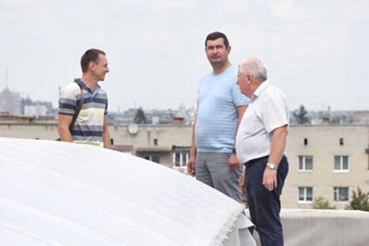 Леонід Карабан таГригорій Недопад інспектують ремонт даху будівлі.