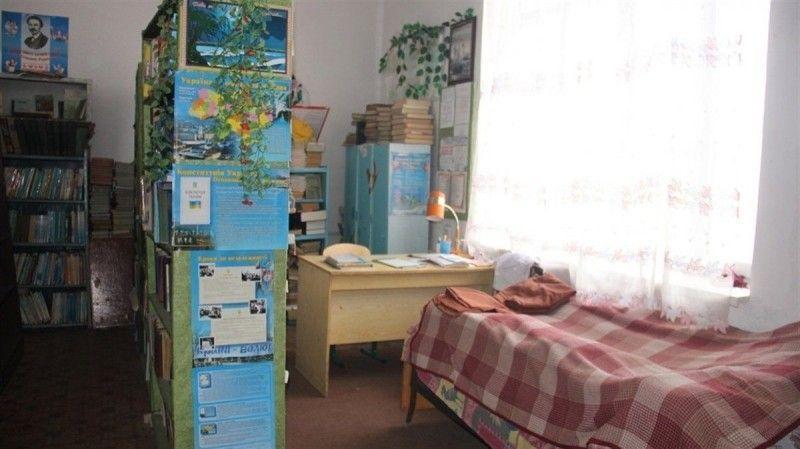 Ліжко педагога поряд зі стелажами.