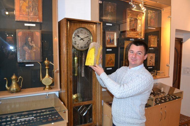 Юрій Фініковський демонструє шматок бивня мамонта, пофарбований жовтою фарбою.