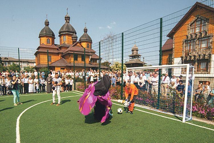 На заняттях футбольної секції душпастир копає м'яча разом із дітьми.