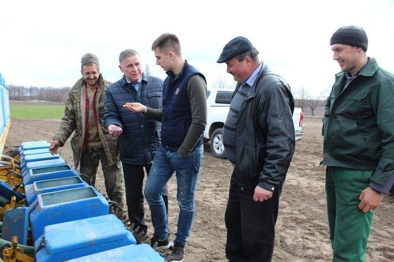 Юрій Горбенко, Олександр Шумський та Микола Романюк з механізаторами біля сівалки.
