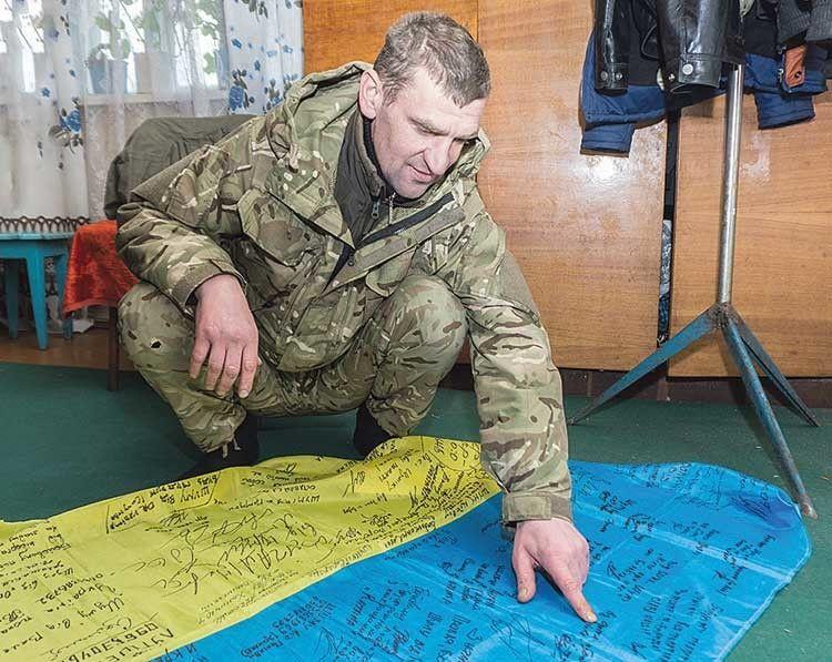 Автографи побратимів на прапорі нагадують про пережите разом.