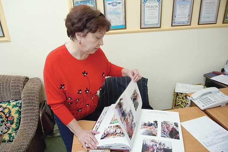 Завідувачка відділення Олена Шушняк гортає альбом зі світлинами, які розповідають про дозвілля мешканців.