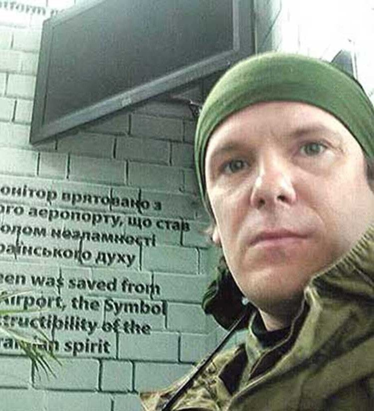 Над головою— монітор, відвойований усепаратистів уДонецькому аеропорту, азаспиною— фото його захисників.