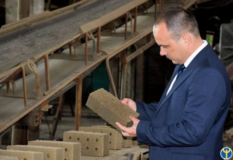 Директор Волинського обласного центру зайнятості Роман Романюк оглядає цеглу, зроблену на Старовижівщині.