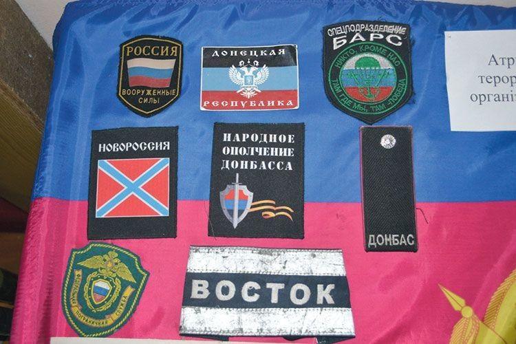 Шеврони та каска терористів — трофеї українських вояків.