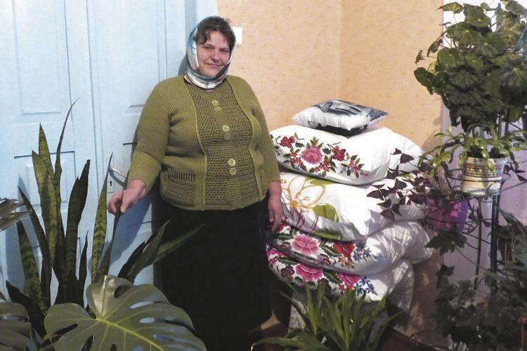 Жінка і сама, як квіточка, у своїй домашній оранжереї, серед вишивок.
