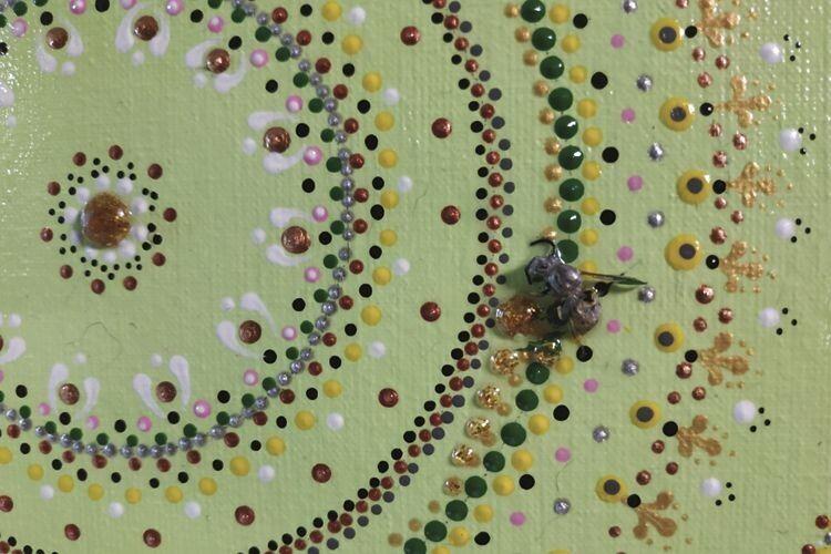 Оригінальна робота збджолою, поруч зякою золоті краплинки «меду».