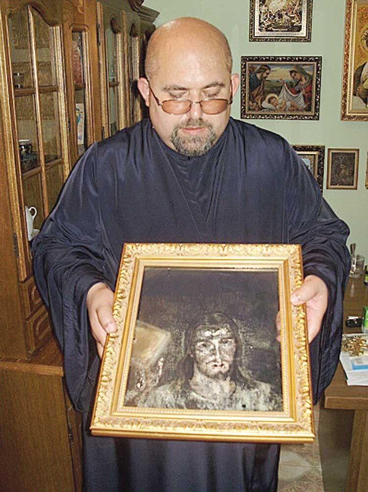 Отець Атанасій демонструє, як на склі цієї ікони відбилося обличчя Ісуса Христа.