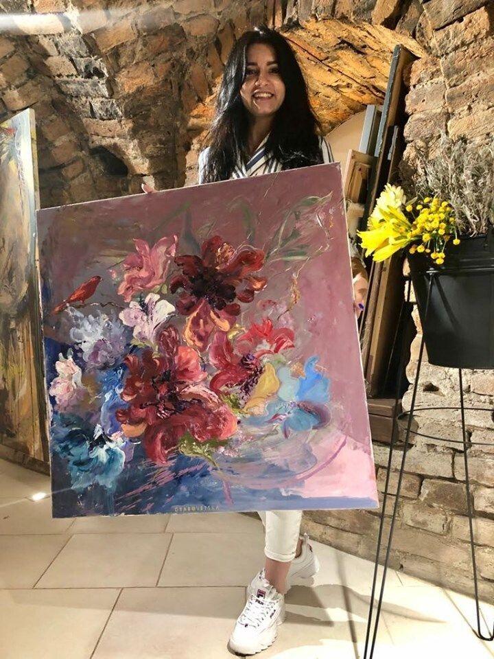 Художниця зі своєю картиною у власній галереї.