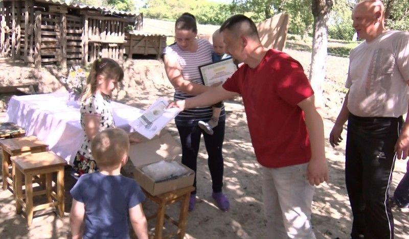 Олексій Дудич (в центрі) пригощає малечу солодощами.